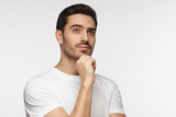 Portrait of young man with dreamy cheerful expression, thinking, isolated over gray background with copy space for your text - 189956824