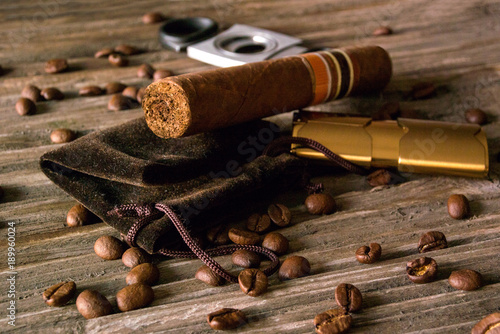Poster Koffiebonen Close-up of cigar, lighter and guillotine with coffee beans on rough wood