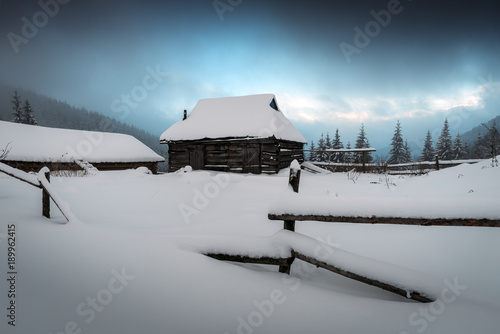 Plexiglas Winter Fantastic winter landscape with wooden house in snowy mountains. Christmas holiday concept. Carpathians mountain, Ukraine, Europe