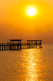 Silhouette of wooden bridge at sunset.