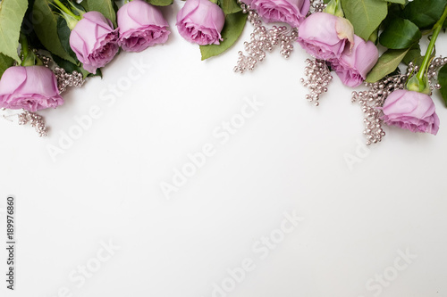 Pink roses flowers on the top of white background with silver beads adornment. Elegant Women's or Mother's Day backdrop .Copyspace concept