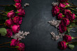 Gothic wedding flowers decor. Dark red or burgundy roses with silver adornment on black background. Bold, daring ,alternative ,and luxury reception party flower arrangement