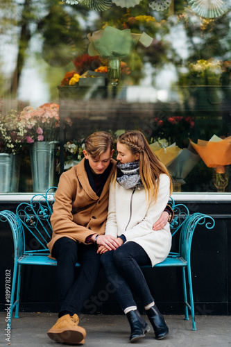 young teen couple on a date. Boyfriend and girlfriend hugging sitting on a bench outdoor. Sweet pure love. Romance true feelings.