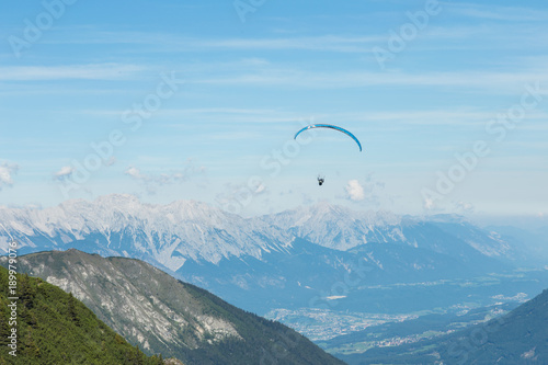 Foto op Aluminium Blauw Paraglider flying near a mountain high above towns below. There are mountains in the background Grass is in the foreground. The setting is cool.