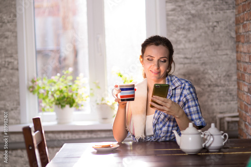 Fototapeta young woman is drinking tea at a table