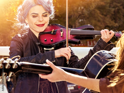 Fotobehang Muziek Music on violin by woman perform in park outdoor. Girl performing jazz on city street. Color tone on shiny sunlight background. Spring outside with blue hairstyle background. Toning of spring photo.