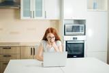 Young female entrepreneur thinking while working at table in her kitchen at home - 189992283