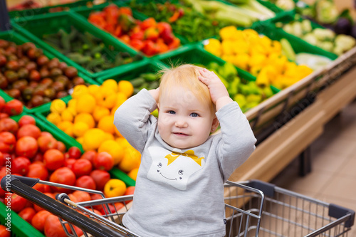 Consumerism concept. Baby in cart doing grocery shopping at supermarket