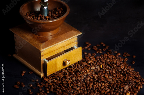 Poster Koffiebonen Coffee beans and an old hand grinder on a black textured background.