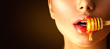 Honey dripping on sexy girl lips from the wooden spoon. Beauty model woman eating honey - 190013477