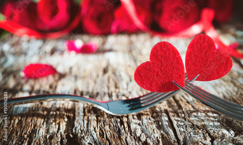 Hearts on forks in front of red roses - 190016283