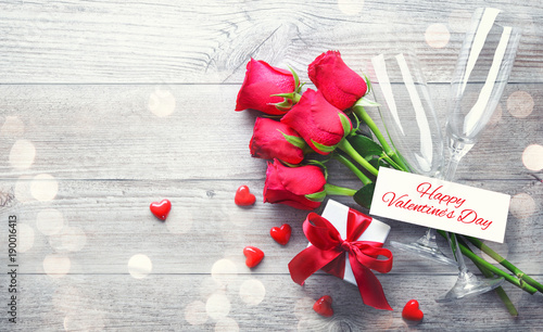 Valentines day greeting card, gift box, red roses and champagne flutes on wooden table - 190016413