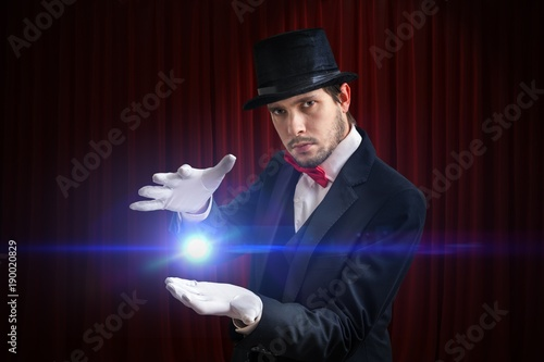 Young magician man is showing bright ball that levitates.