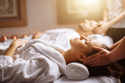 Leinwanddruck Bild Young couple receiving head massage at beauty spa