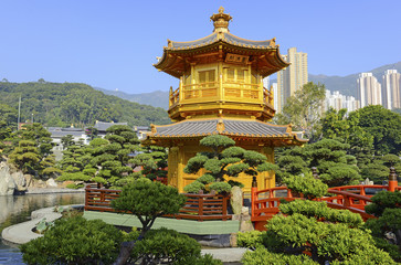 Traditional Chinese Pagoda with bridge in Chinese garden with city skyline, in Hong Kong, China