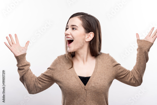 Overflowing with emotions. Adorable upbeat young woman raising her hands and shouting with joy while posing isolated on a white background