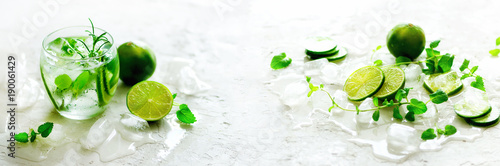 Homemade lime lemonade with cucumber, rosemary and ice, white background. Cold beverage, detox water. Copyspace. Banner - 190061429