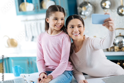 Time together. Beautiful joyful dark-haired mother and daughter smiling and taking selfies while girl sitting on the table