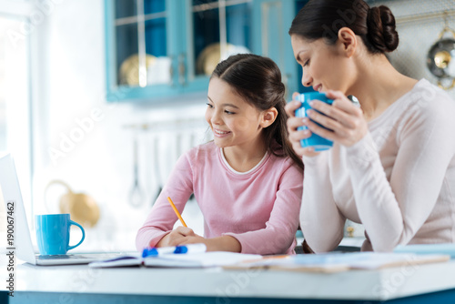 Happy moments. Pretty inspired dark-haired schoolgirl writing in her notebook and smiling while her mother standing near her