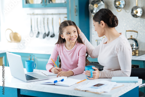 Caressing. Pretty alert dark-haired schoolgirl writing in her notebook and smiling at her mother standing near the girl with a cup of tea and caressing her
