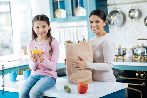 Favourite food. Attractive inspired dark-haired woman holding a packet and smiling and her alert daughter holding a pepper