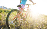 Young girl with a sports bike in the sunlight - 190070043