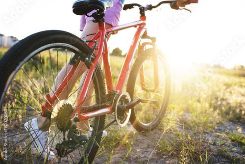chica-joven-con-una-bicicleta-deportiva-en-la-luz-del-sol