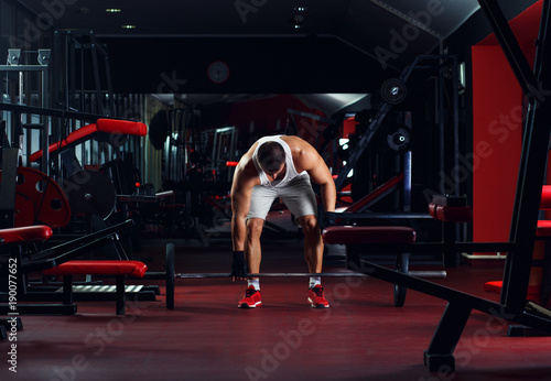 Sticker Young man exercising with barbell weight in the gym.