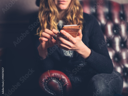 Woman on leather sofa using phone