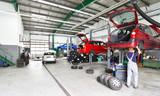 Reifenwechsel und Reparatur von Autos in einer Werkstatt - Aussstattung und Mechaniker arbeitet am Fahrzeug auf einer Hebebühne - 190081453