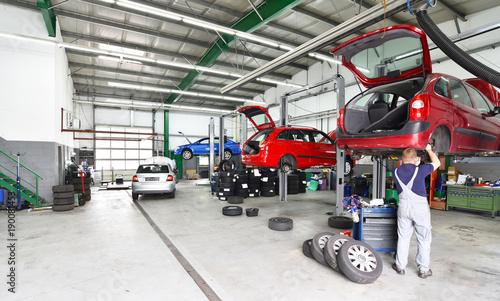 Reifenwechsel und Reparatur von Autos in einer Werkstatt - Aussstattung und Mechaniker arbeitet am Fahrzeug auf einer Hebebühne