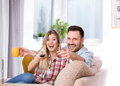 Couple watching tv and laughing Poster