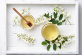 White wooden tray with sweet honey jar and spring acacia blossoms, top view - 190091885