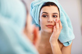 Young woman standing in bathroom and applying face cream in the morning - 190095488