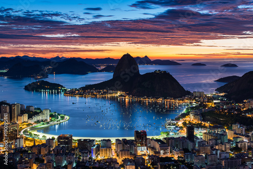 Rio de Janeiro city just before sunrise with city lights on, and the Sugarloaf Mountain in the horizon
