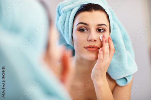 Young woman standing in bathroom and applying face cream in the morning