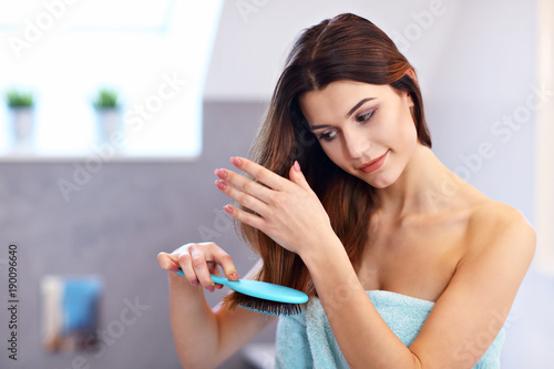 In de dag Kapsalon Young woman standing in bathroom and brushing hair