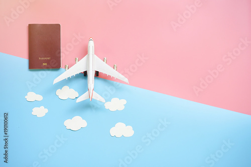 Flat lay design of travel concept with plane, passport and cloud on blue and pink background with copy space.