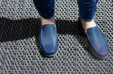 A man in blue jeans and moccasins. Blue moccasins of leather