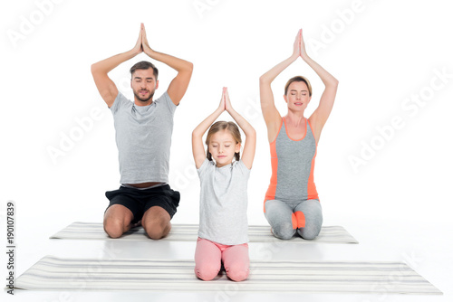 athletic family practicing yoga on mats together isolated on white