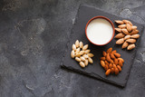 Almond milk in a clay pot and fresh nuts over dark slate background, selective focus. Dairy-free, vegan healthy food concept - 190114647