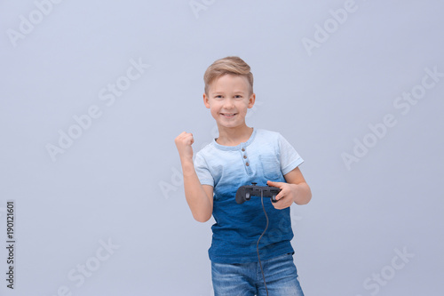 Happy boy with video game controller on color background