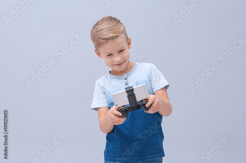 Cute boy with video game controller for smartphone on color background