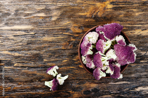 purple cauliflower in a clay plate, on a wooden table. top view