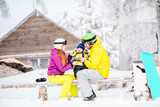 Happy family with baby boy in winter spots clothes sitting on the bench outdoors during the winter vacations - 190134268