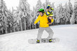 Quadro Man in colorful sports clothes riding the snowboard on the snowy mountains with beautiful trees on the background