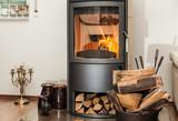 Fototapeta Las - Innendekoration mit brennendem Kamin und gelagerten Holzscheiten im Wohnzimmer © Lilli