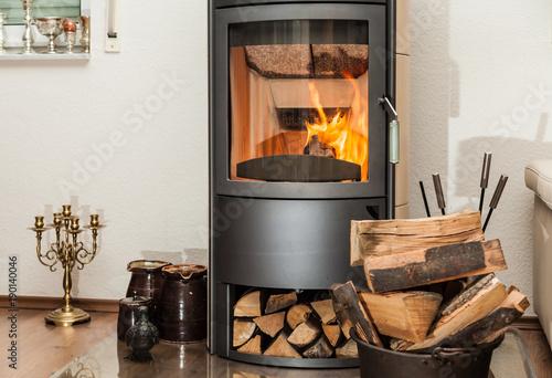 Innendekoration mit brennendem Kamin und gelagerten Holzscheiten im Wohnzimmer - 190140046