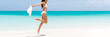 Happy beach body woman jumping of joy with sun hat on caribbean travel vacation. Slim legs sexy bikini girl sun tanning feeling free. Banner panorama with copy space on blue ocean background