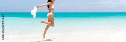 Szczęśliwy plażowy ciało kobiety doskakiwanie radość z słońce kapeluszem na karaibskim podróż wakacje. Szczupłe nogi sexy bikini dziewczyna opalania czuje się wolna. Sztandar panorama z kopii przestrzenią na błękitnym oceanu tle